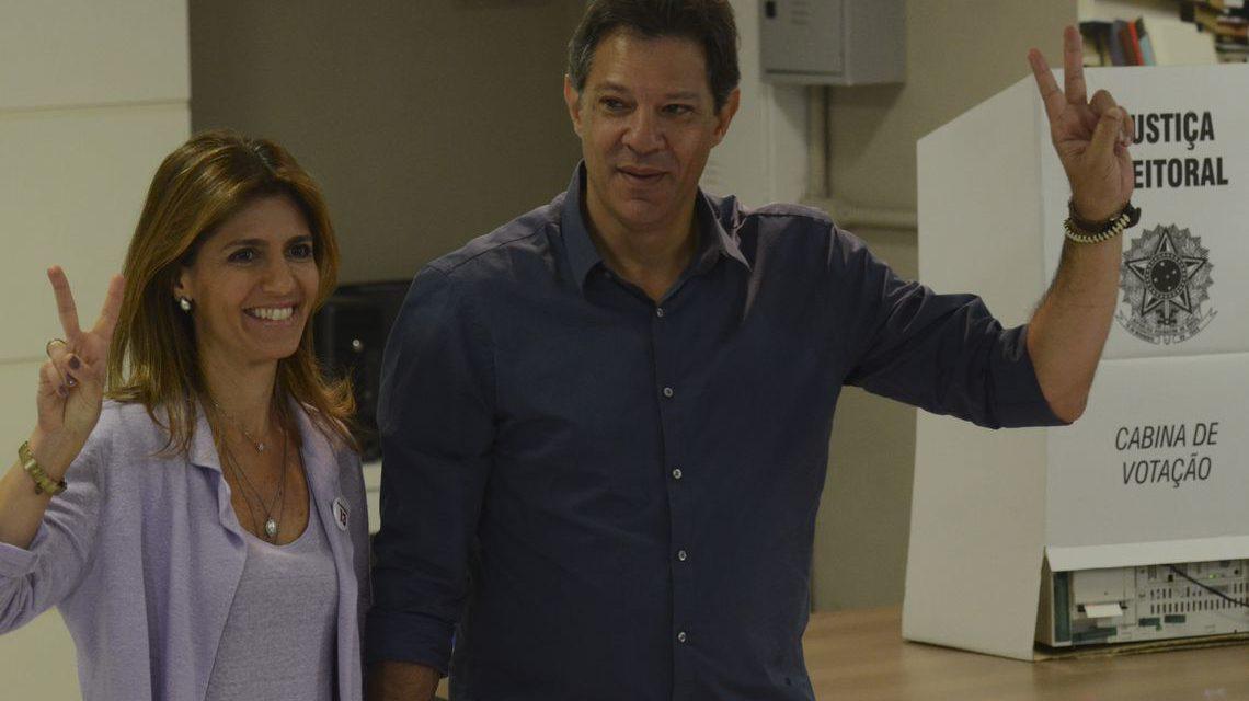 Com camisa azul, Haddad vota e faz sinal de vitória
